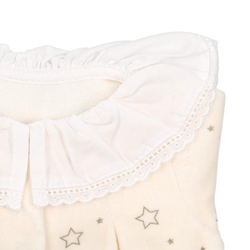 Pormenor da gola em tecido branco com renda de babygrow pijama de bebé de cor pérola.