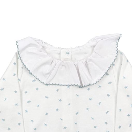 Pormenor da gola em tecido de babygrow de bebé branco cru com estrelas azuis.