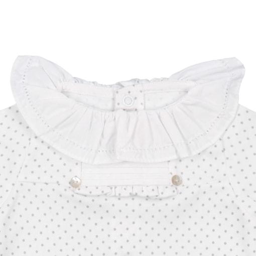 Pormenor da gola em tecido branco de um babygrow de bebé branco com pintas cinzentas.