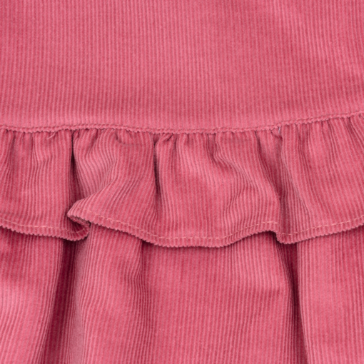Pormenor de um Fofo para bebe em bombazine cor de rosa com folho à volta.