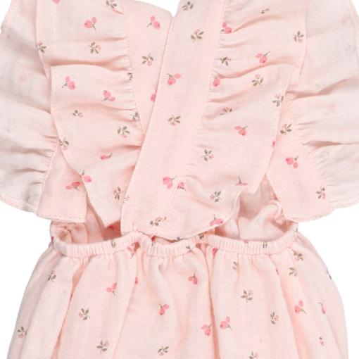 Alças a cruzar nas costas de Fofo de bebé em tecido rosa com estampado em flores. Tem folhos nas alças e é feito em tecido 100% algodão orgânico.