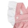 Folho branco nas alças de um fofo de bebé em tecido de algodão rosa claro com um padrão de estrelas brancas estampado. Tem botões de massa branca nas alças.