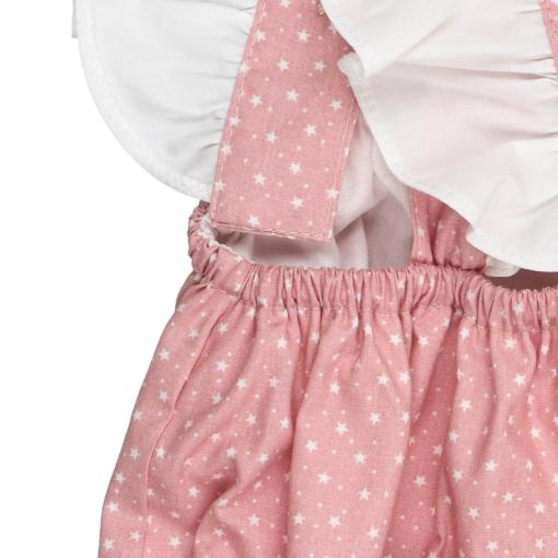Elástico na cintura de um fofo de bebé em tecido de algodão rosa claro com um padrão de estrelas brancas estampado.