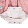 Forro branco e molas de pressão do entre-pernas de um fofo de bebé em tecido de algodão rosa com estrelas brancas estampadas.