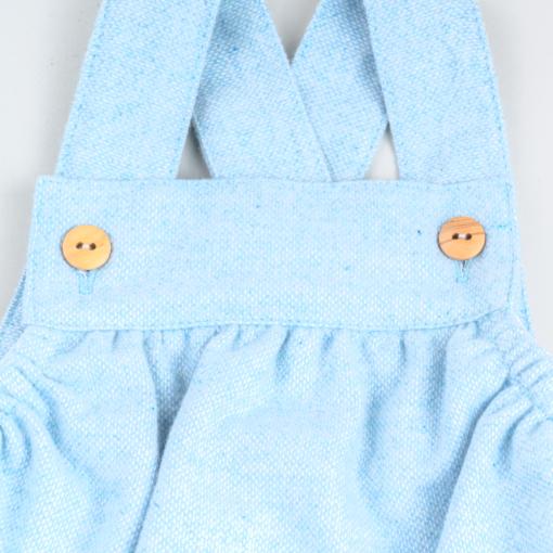 Pormenor das alças de um fofo de bebé azul claro em fazenda com botões de madeira nas alças.