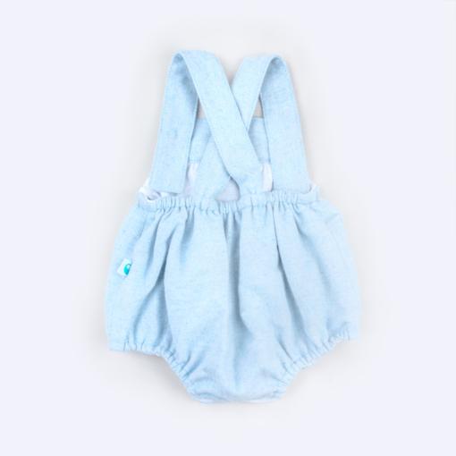 Vista de trás de fofo de bebé azul claro em fazenda com as alças a cruzar nas costas.