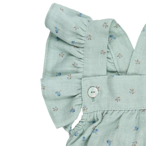 Folho nas alças de um fofo de bebé de cor verde com estampado em flores.