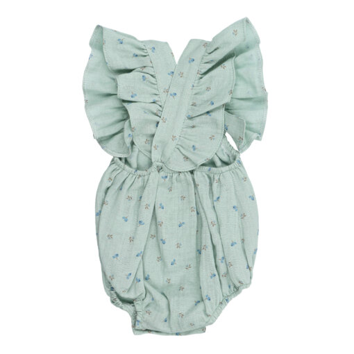 Vista de trás de fofo de bebé com folhos nas alças verde com estampado de flores feito em tecido de algodão orgânico.