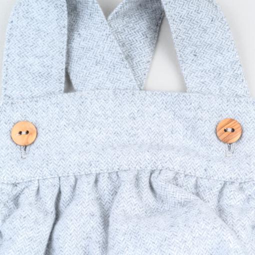 Pormenor de fofo de bebé em fazenda de cor cinzenta mesclado a mostrar os botões em madeira nas alças.