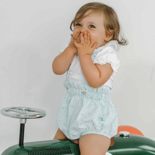 Bebé vestida com fofo de alças e body sentada em um carrinho.