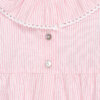 Botões de madrepérola nas costas de um fofo de bebé rosa às riscas brancas.