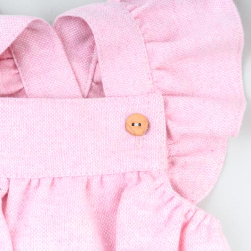 Vista de pormenor da alças com folhos e botões de madeira de um fofo de bebé feito em fazenda rosa.
