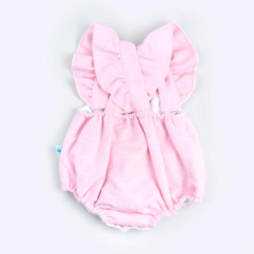 Vista de trás de fofo de bebé em fazenda rosa com as alças a cruzar nas costas.