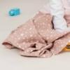 Bebé com fralda de pano rosa velho com estrelas brancas.