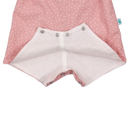 Vista do entre-pernas com três molas de pressão e do forro interior branco de umas jardineiras de bebé rosa com estampado em estrelas brancas.