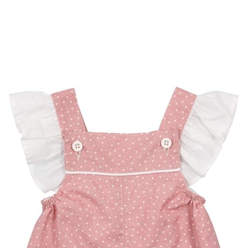 Vista das alças com folhos de uma jardineiras de bebé rosa com estampado de estrelas brancas.
