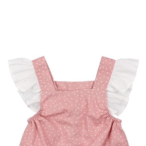 Vista de trás das alças com folhos de uma jardineiras de bebé rosa com estampado de estrelas brancas.