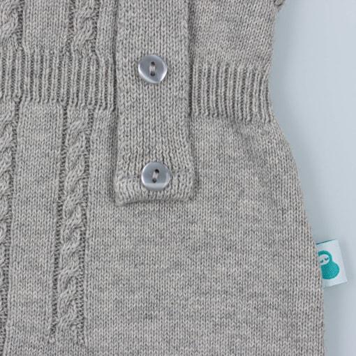 Pormenor dos botões nas alças de umas jardineiras de malha para bebé de cor cinzenta.