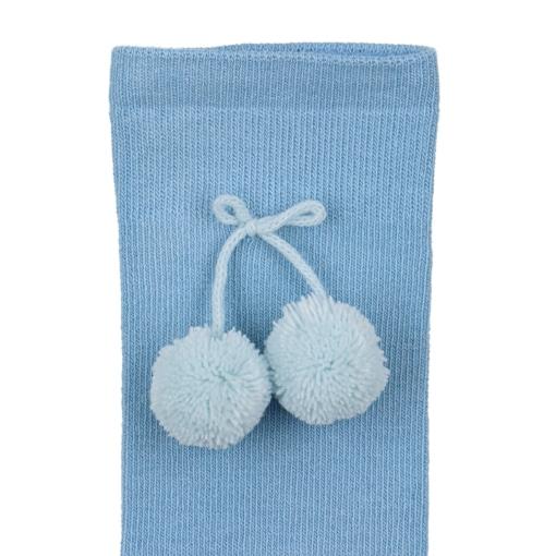 Pormenor dos Pom Pons de meias altas para bebé de cor azul claro.