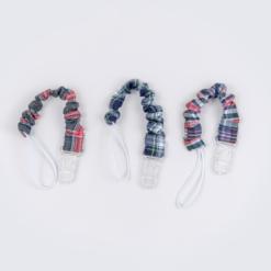 Porta chupetas para bebé em tecido xadrez e com o fecho em plástico transparente.