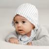 Bebé de gatas com uma touca de tecido às riscas brancas e cinzentas.