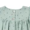 Vista dos botões em madrepérola de vestido de bebé em tecido verde com estampados de flores feito em tecido 100% algodão orgânico.